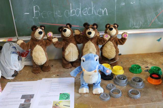 Vier Braunbären und ein Dino-Spielzeug warten auf ihren Umbau. Rechts sind unfertige Tastergehäuse zu sehen.