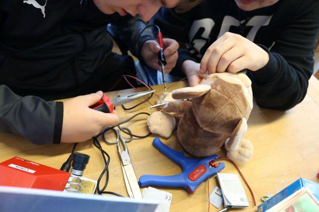 Zwei Schüler bearbeiten mit Zange und Lötkolben einen unschuldigen Affen. Pulp Fiction Referenz! Telefonstreich! Telefonstreich!